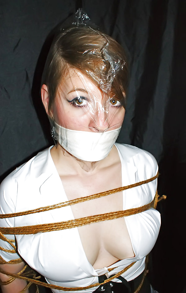 Lesbian domme is wrapping her mate with plastic tape getting ready to fuck her mouth with a strapon