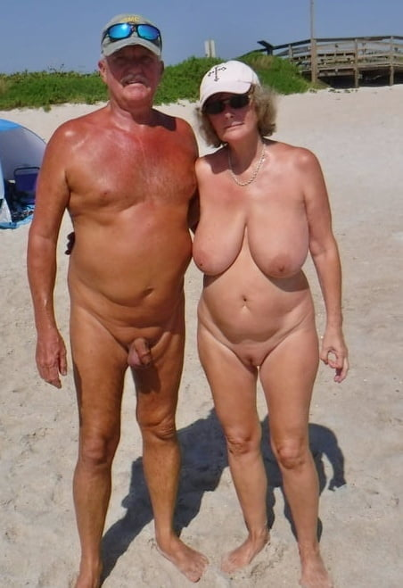Happy nudist couple naked on holiday beach