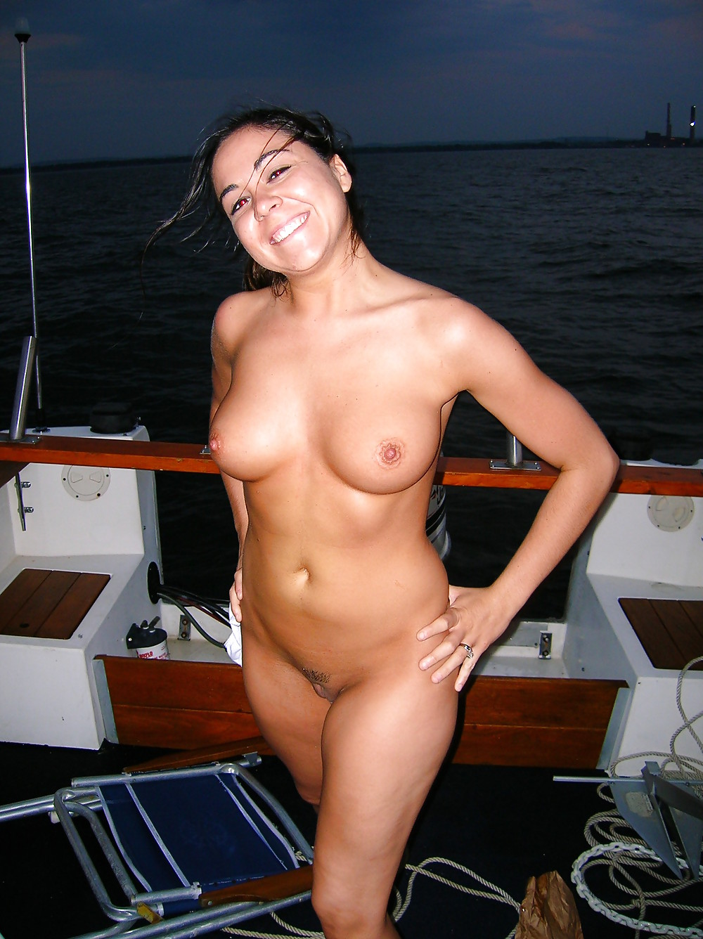 busty brunette posing naked on a boat