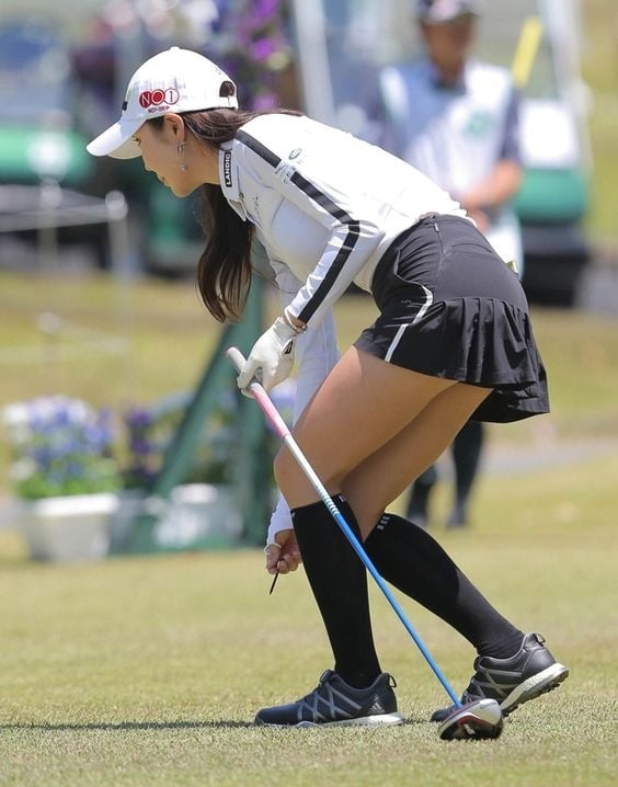 Sexy golf player woman with both hands on the golf club stock photograph